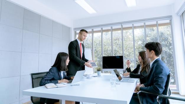 A los jóvenes empresarios se les presenta un proyecto de trabajo de mercadeo al cliente en la oficina de la sala de reuniones