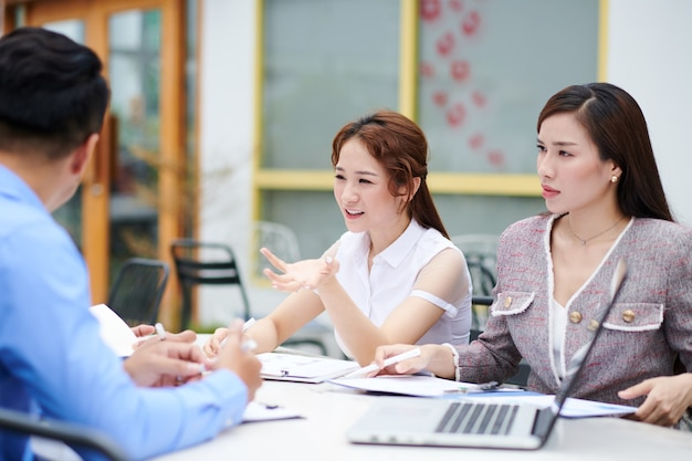 Jóvenes empresarios serios reuniéndose con colegas y discutiendo documentos, informes e ideas para el desarrollo empresarial