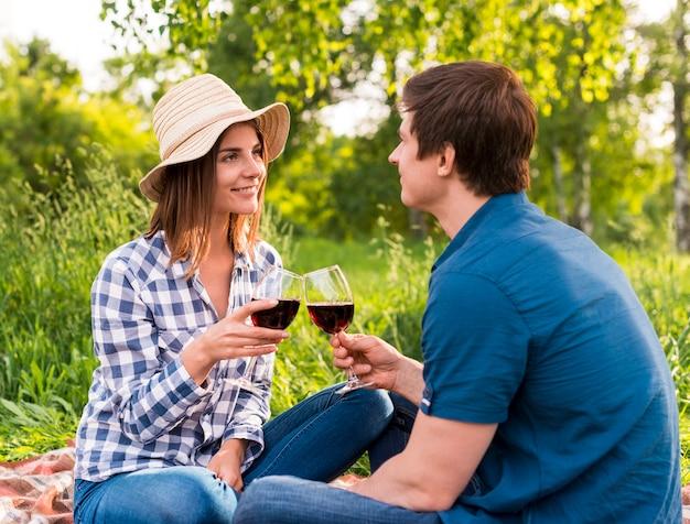 Jóvenes enamorados saliendo afuera con copas.