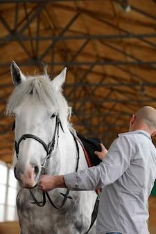 Los jóvenes en un entrenamiento de caballos en una arena de madera