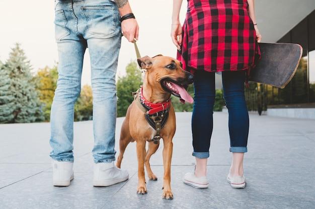 Los jóvenes en la escena urbana pasean al perro. hombre joven con un perro con correa y una mujer joven con una patineta al aire libre: concepto de cultura juvenil que las personas son responsables y tienen una mascota