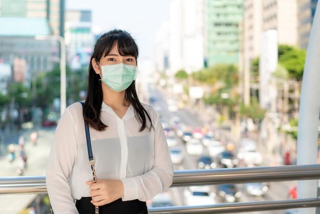 Jóvenes estresan a una empresaria asiática con camisa blanca que va a trabajar en una ciudad contaminada, usa una máscara de protección para evitar el polvo, el smog, la contaminación del aire y el covid-19 pm2.5