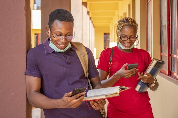 Jóvenes estudiantes africanos con mascarillas y sosteniendo libros y teléfonos en un campus