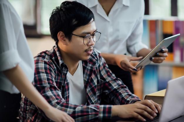 Jóvenes estudiantes aprendiendo, bibliotecas de estanterías.