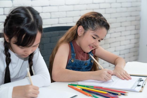 Jóvenes estudiantes asiáticas aprendiendo y haciendo la tarea en el libro en el aula de la escuela primaria