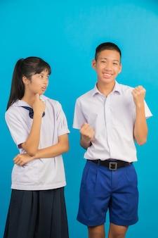 Jóvenes estudiantes asiáticos y estudiantes varones asiáticos se unen en un azul.