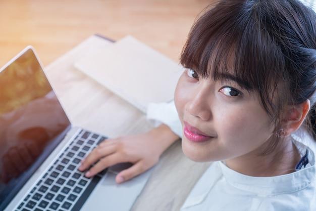 Jóvenes estudiantes asiáticos hermosos o blogger estudiando con computadora portátil