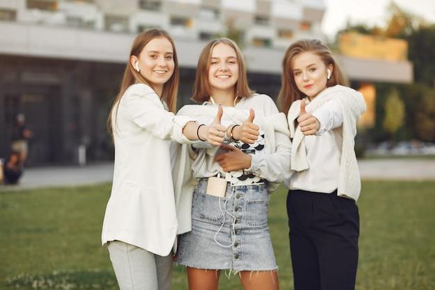 Jóvenes estudiantes en un campus de estudiantes mostrando los pulgares para arriba