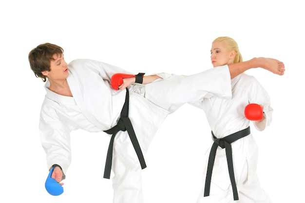 Jóvenes estudiantes de karateka en kimono blanco, cinturones negros en guantes de combate entrenan para practicar golpes con patadas y manos sobre un fondo blanco.
