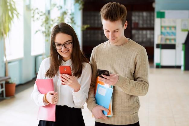 Jóvenes estudiantes masculinos y femeninos de secundaria jugando con sus teléfonos inteligentes