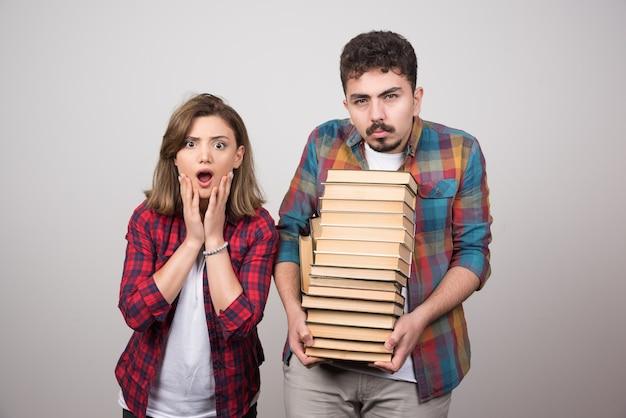Jóvenes estudiantes mirando sorprendidos y sosteniendo libros sobre fondo gris.
