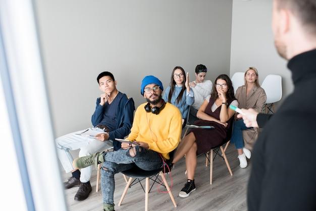 Jóvenes estudiantes multiétnicos que estudian en clase de entrenamiento