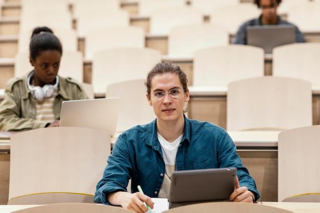 Jóvenes estudiantes que asisten a una clase universitaria.