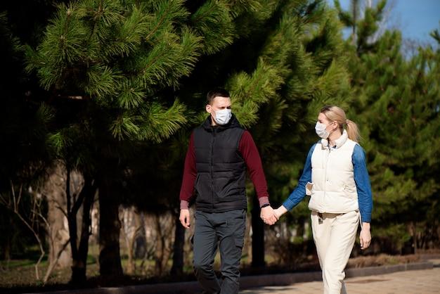 Jóvenes europeos, hombre y mujer con máscara médica desechable protectora caminando al aire libre, temerosos del peligroso coronavirus de la gripe mutado y propagado en china