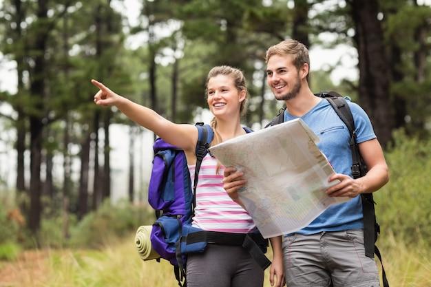 Jóvenes excursionistas felices apuntando en la distancia con un mapa