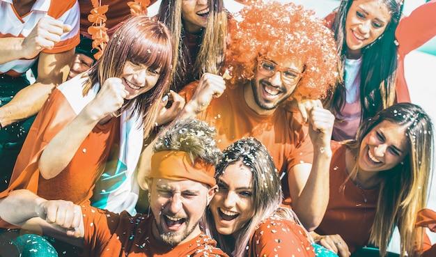 Jóvenes fanáticos del fútbol que animan con bandera y confeti viendo el partido de la copa de fútbol en el estadio