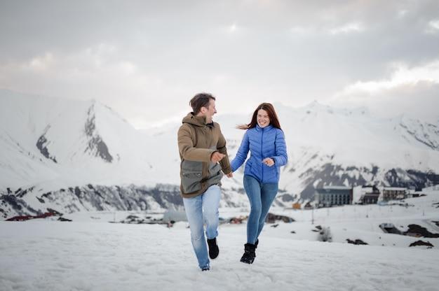 Jóvenes y felices amantes en el invierno pasando tiempo en las montañas