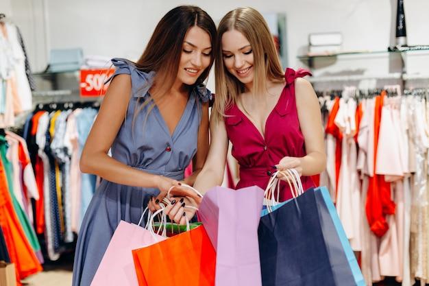 Jóvenes y felices chicas de compras con bolsas de colores considerando comprar