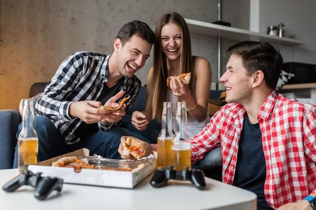 Jóvenes felices comiendo pizza, bebiendo cerveza, divirtiéndose, fiesta de amigos en casa, compañía hipster juntos, dos hombres una mujer, sonriendo, positivo, relajado, pasar el rato, reír,