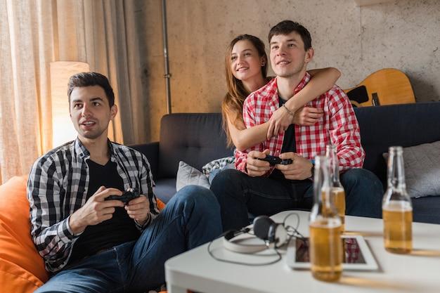 Jóvenes felices jugando videojuegos, divirtiéndose, fiesta de amigos en casa, cerca de las manos sosteniendo el joystick, compañía hipster juntos, sonriendo, positivo, riendo, competencia, botellas de cerveza en la mesa