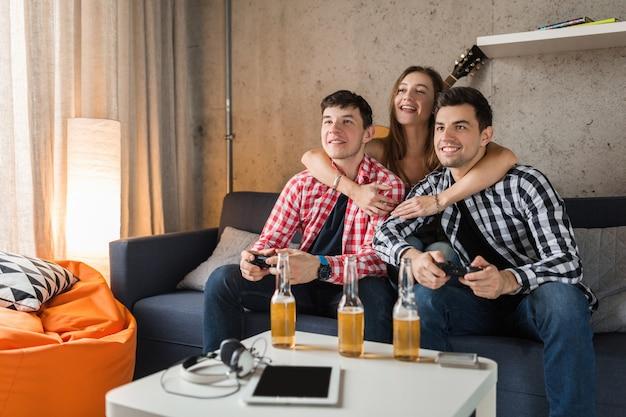 Jóvenes felices jugando videojuegos, divirtiéndose, fiesta de amigos en casa, compañía hipster juntos, dos hombres una mujer, sonriente, positivo, relajado, emocional, riendo, competencia