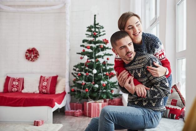 Los jóvenes felices se sientan en el alféizar de la habitación con adornos navideños y se abrazan