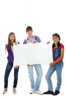 Jóvenes felices sujetando un anuncio en blanco