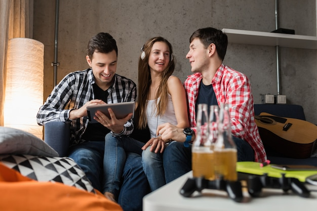 Jóvenes felices usando tableta, estudiantes aprendiendo, divirtiéndose, fiesta de amigos en casa, compañía hipster juntos, dos hombres y una mujer, sonriendo, positivo, educación en línea, escuchando música