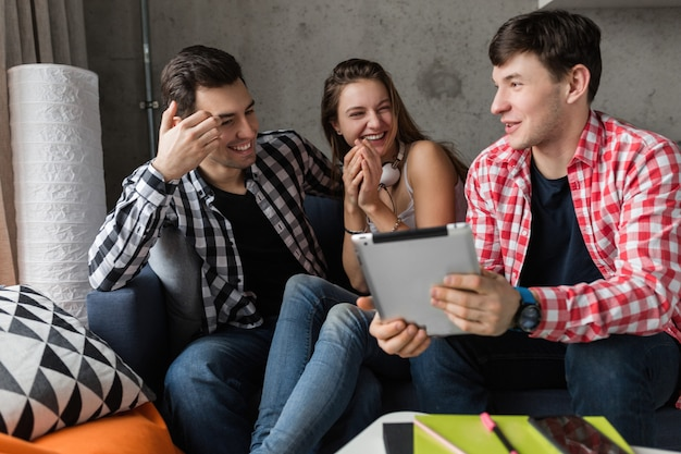 Jóvenes felices usando tableta, estudiantes aprendiendo, divirtiéndose, fiesta de amigos en casa, compañía hipster juntos, dos hombres una mujer, sonriendo, positivo, educación en línea, riendo