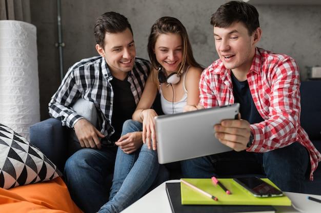 Jóvenes felices usando tableta, estudiantes aprendiendo, divirtiéndose, fiesta de amigos en casa, compañía hipster juntos, dos hombres una mujer, sonriendo, positivo, educación en línea