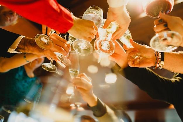 Jóvenes festejando haciendo tostadas con vasos y bebiendo alcohol.