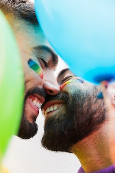 Jóvenes gays sonriendo mientras se besan
