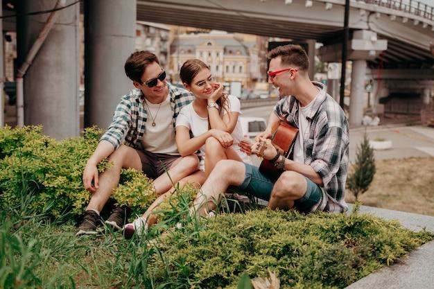 Los jóvenes con una guitarra se divierten sentados en el césped