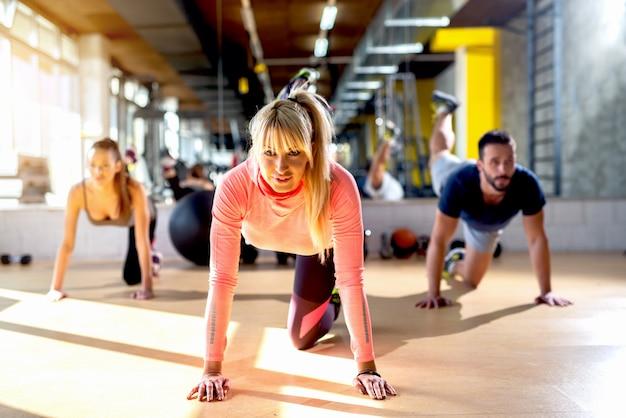 Jóvenes haciendo ejercicios en clase deportiva trabajando duro