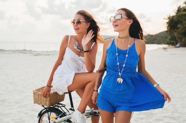 Jóvenes hermosas chicas hipster divirtiéndose en la playa