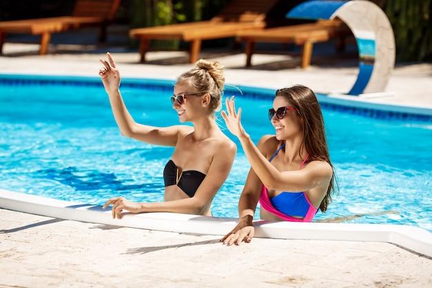 Jóvenes hermosas chicas sonriendo, saludo, relajarse en la piscina.