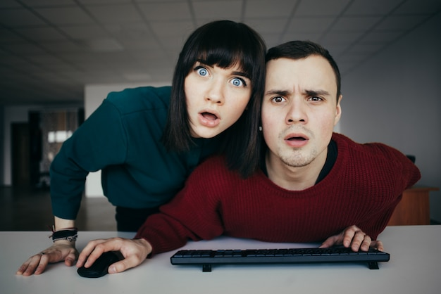 Jóvenes hermosas miradas perplejas en el monitor de la computadora. mirada emocional a la cámara