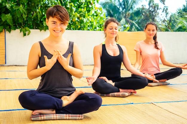 Jóvenes hermosas mujeres practican meditación grupal en clase de yoga