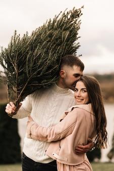 Jóvenes hermosos amantes felices hombre y mujer, historia de amor en invierno con un árbol de navidad vivo en sus manos en el fondo de la orilla del río