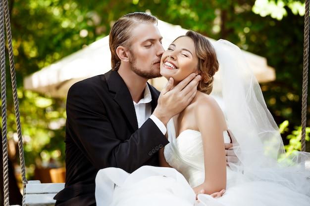 Jóvenes hermosos recién casados sonriendo, besando, sentado en el columpio en el parque.