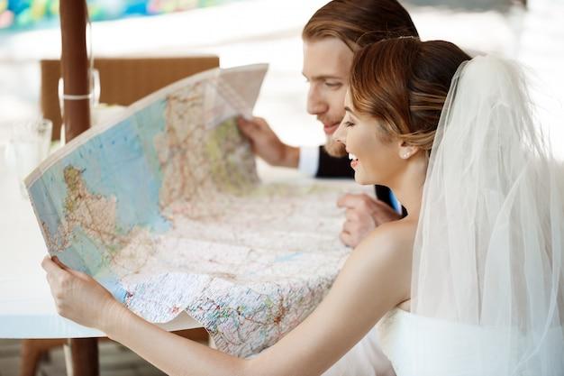 Jóvenes hermosos recién casados sonriendo, elegir viaje de luna de miel, mirando el mapa.