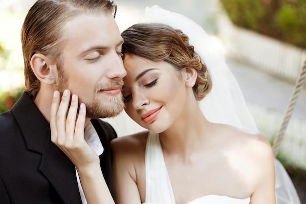 Jóvenes hermosos recién casados sonriendo con los ojos cerrados, disfrutando.