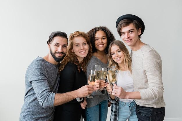 Jóvenes hombres y mujeres alegres y amigables que celebran las vacaciones mientras brindan con flautas de champán espumoso