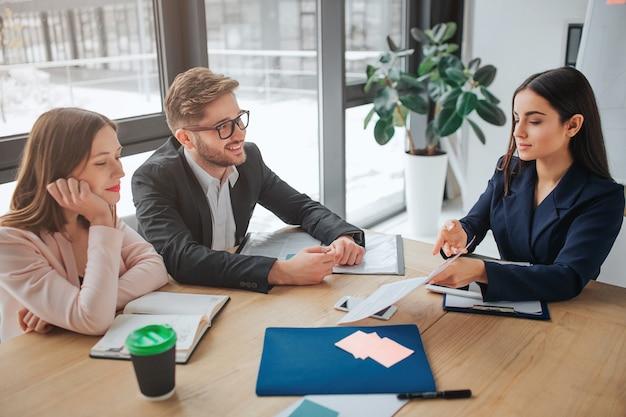 Jóvenes, hombres y mujeres se sientan juntos a la mesa en la sala de reuniones