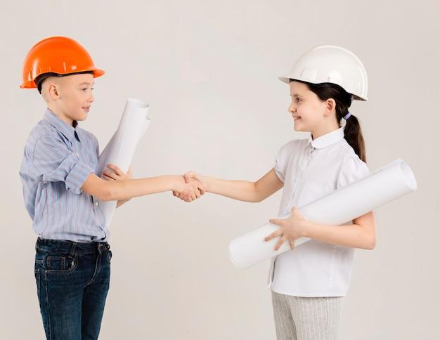 Jóvenes ingenieros agitando las manos