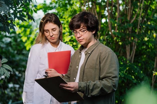 Jóvenes ingenieros agrícolas trabajando en invernadero
