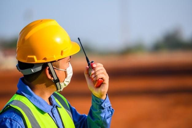 Los jóvenes ingenieros asiáticos utilizan las comunicaciones por radio para controlar el transporte industrial y la logística.