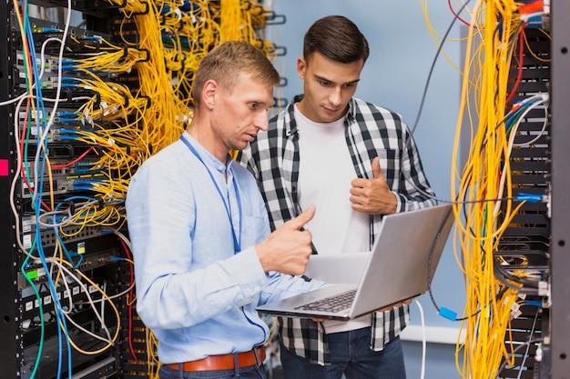 Jóvenes ingenieros de red con una computadora portátil de tiro medio