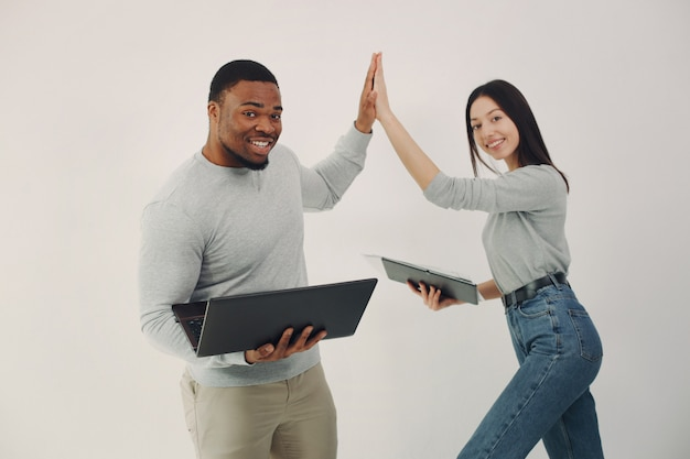 Jóvenes internacionales que trabajan juntos y usan la computadora portátil