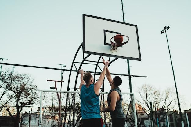 Jóvenes jugadores de baloncesto jugando uno a uno.